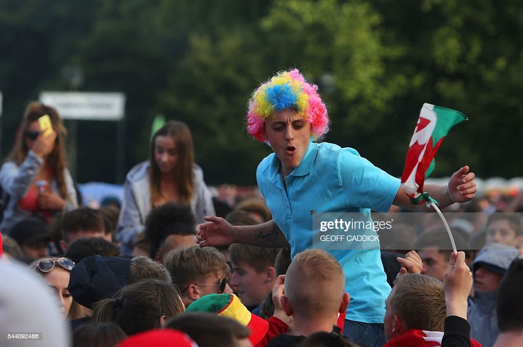 Wales fans prepare for the screening of the Euro 2016 quarter final match between Wales and Belgium at the fan zone in Cardiff, south Wales on July 1, 2016. / AFP / Geoff CADDICK