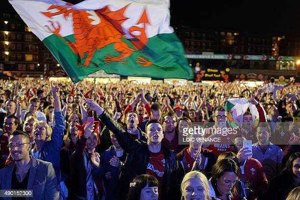 Wales fans react as they watch the England v Wales rugby union game on a giant television screen at a fanzone in Cardiff Wales on September 26 during...