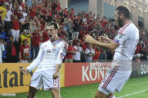 Wales forward Gareth Bale celebrates with teammate midfielder Joe Ledley after scoring a goal during the Euro 2016 qualifying round football match...