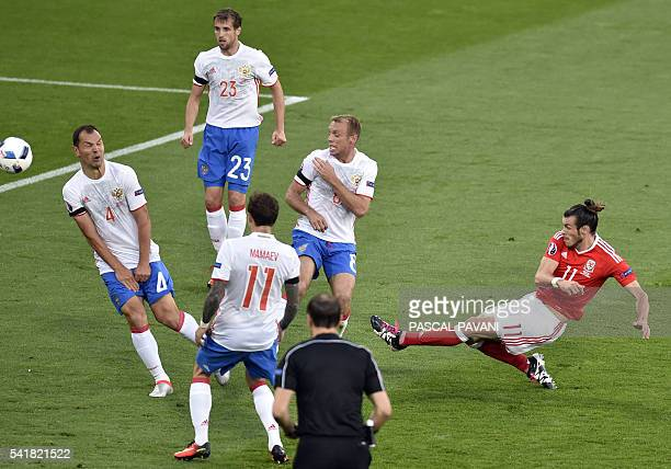 Wales' forward Gareth Bale shoots the ball past Russia's defender Sergey Ignashevich during the Euro 2016 group B football match between Russia and...