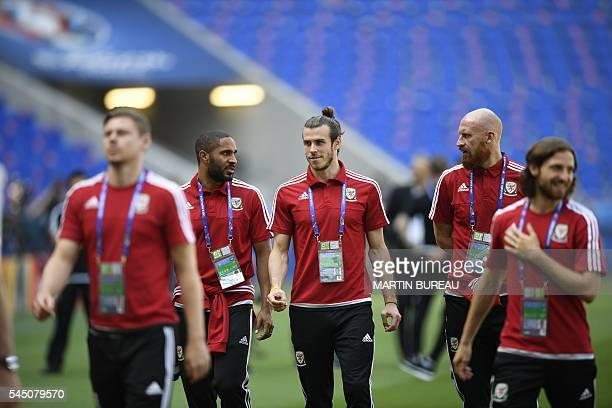 Wales' forward Gareth Bale speaks to defender Ashley Williams next to Wales' defender James Collins during a training session at the Parc Olympique...