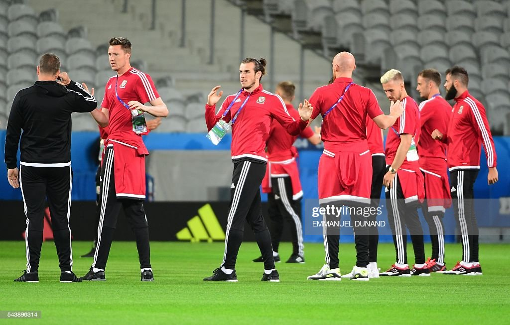 Wales' forward Gareth Bale (C) stretches with teammates while walking around the Pierre-Mauroy stadium ahead of the match between Wales and Belgium during the Euro 2016, in Villeneuve-d'Ascq near Lille on June 30, 2016. / AFP / EMMANUEL