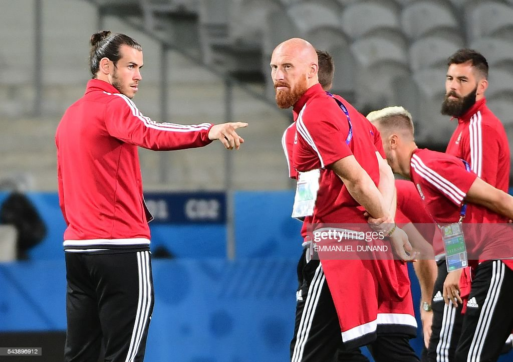Wales' forward Gareth Bale (L) talks with Wales' defender James Collins (C) teammates while walking around the Pierre-Mauroy stadium ahead of the match between Wales and Belgium during the Euro 2016, in Villeneuve-d'Ascq near Lille on June 30, 2016. / AFP / EMMANUEL