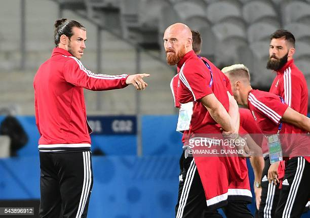 Wales' forward Gareth Bale talks with Wales' defender James Collins teammates while walking around the PierreMauroy stadium ahead of the match...