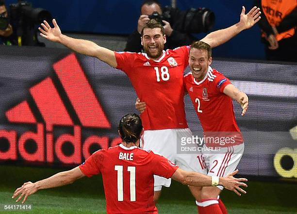 Wales' forward Sam Vokes celebrates with teammates after scoring a goal during the Euro 2016 quarterfinal football match between Wales and Belgium at...
