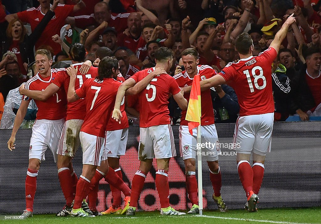 Wales' forward Sam Vokes (R) celebrates with teammates after scoring his team's third goal during the Euro 2016 quarter-final football match between Wales and Belgium at the Pierre-Mauroy stadium in Villeneuve-d'Ascq near Lille, on July 1, 2016. / AFP / PHILIPPE