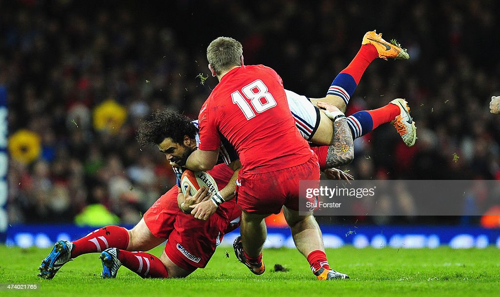 Wales forwards Paul James (hidden) and Rhodri Jones combine to tackle France wing Yoann Huget during the RBS Six Nations match between Wales and France at Millennium Stadium on February 21, 2014 in Cardiff, Wales.