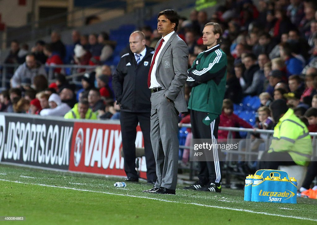 Wales' manager Chris Coleman (C) and Finland's manager Mixu Paatalainen (L) stand on the sideline as they attend the international friendly football match between Wales and Finland at Cardiff City Stadium in Cardiff, south Wales on November 16, 2013. The match ended 1-1. AFP PHOTO / GEOFF CADDICK