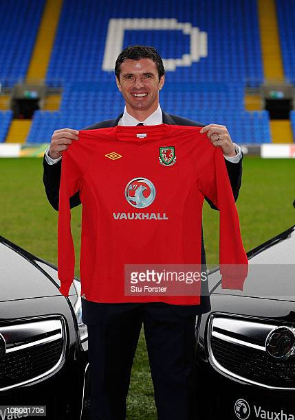 Wales manager Gary Speed holds up the team shirt at the launch of the announcment of Vauxhall as the new team sponsor at Cardiff City Stadium on...