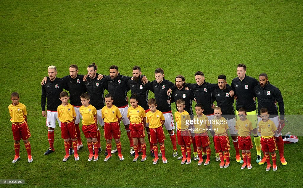 Wales' midfielder Aaron Ramsey, defender Chris Gunter, forward Gareth Bale, forward Hal Robson-Kanu, midfielder Joe Ledley, defender Ben Davies, midfielder Joe Allen, defender James Chester, defender Neil Taylor, goalkeeper Wayne Hennessey and defender Ashley Williams listen to their national anthem ahead of the Euro 2016 quarter-final football match between Wales and Belgium at the Pierre-Mauroy stadium in Villeneuve-d'Ascq near Lille, on July 1, 2016. / AFP / Denis Charlet