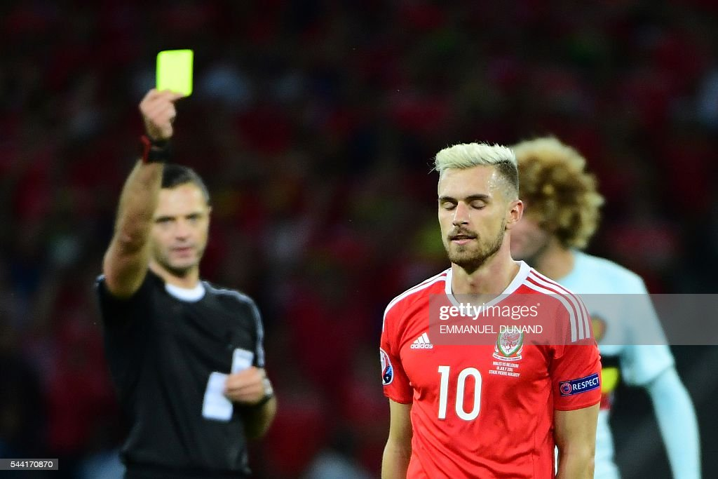 Wales' midfielder Aaron Ramsey is shown a yellow card during the Euro 2016 quarter-final football match between Wales and Belgium at the Pierre-Mauroy stadium in Villeneuve-d'Ascq near Lille, on July 1, 2016. / AFP / EMMANUEL