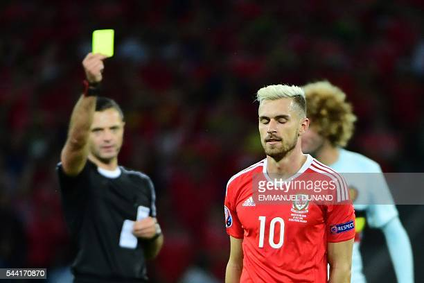 Wales' midfielder Aaron Ramsey is shown a yellow card during the Euro 2016 quarterfinal football match between Wales and Belgium at the PierreMauroy...