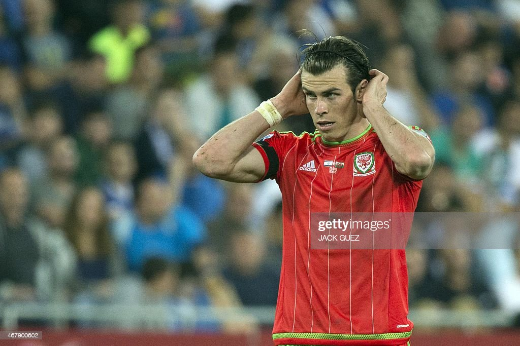 Wales' midfielder Gareth Bale fixes his hair before taking a free kick during the Euro 2016 qualifying football match between Israel and Wales at the...