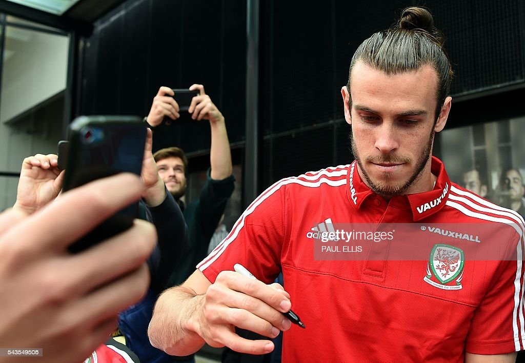 Wales' midfielder Gareth Bale signs autographs for local youngsters after attending a press conference in Dinar on June 29, 2016 during the Euro 2016 football tournament. / AFP / PAUL