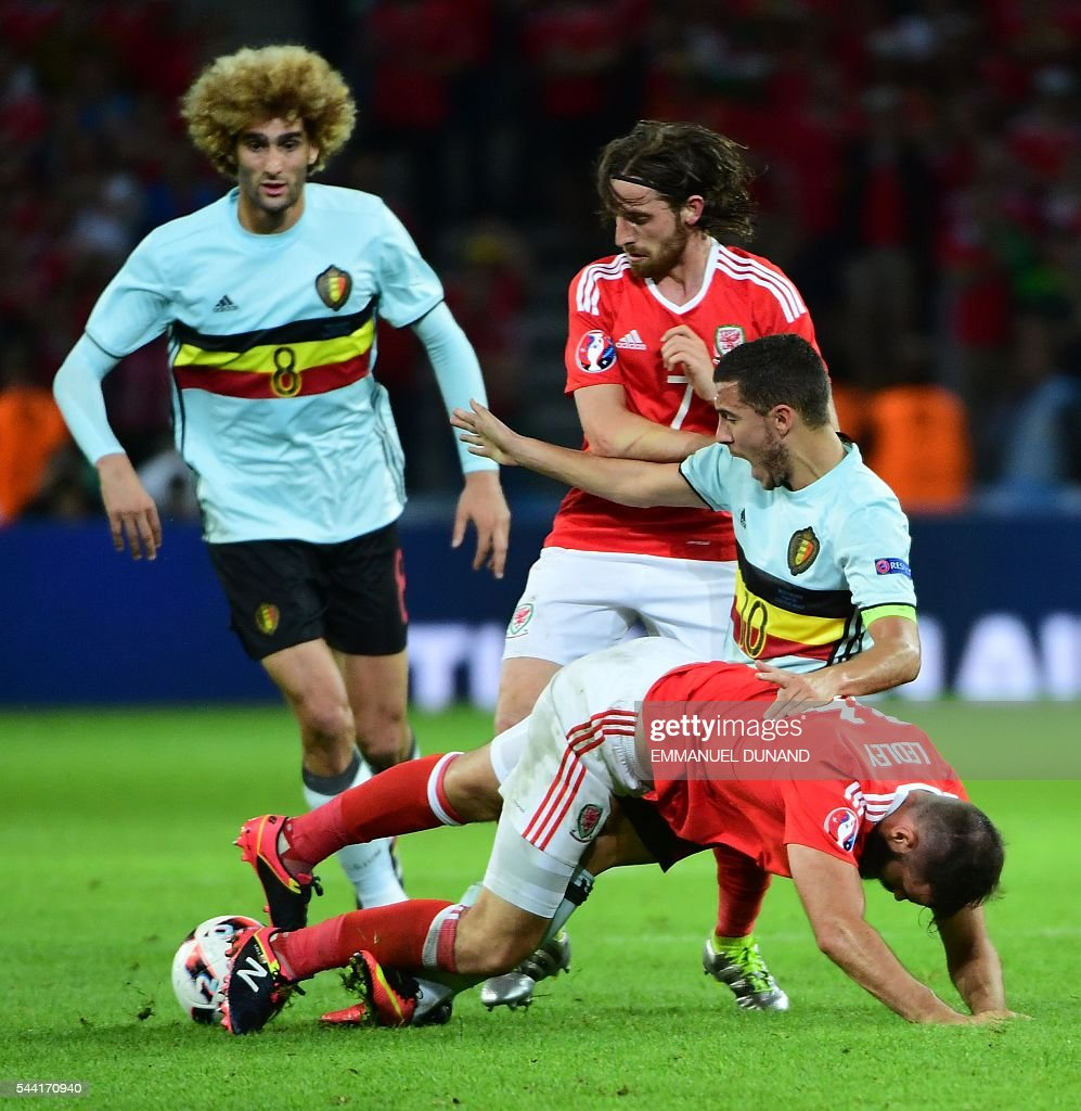 Wales' midfielder Joe Ledley (front) and Belgium's forward Eden Hazard vie for the ball during the Euro 2016 quarter-final football match between Wales and Belgium at the Pierre-Mauroy stadium in Villeneuve-d'Ascq near Lille, on July 1, 2016. / AFP / EMMANUEL