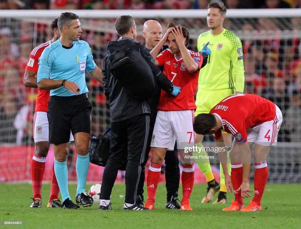 Wales physiotherapists see to Joe Allen (C) who suffered a suspected head injury during the FIFA World Cup Qualifier Group D match between Wales and Republic of Ireland at The Cardiff City Stadium on October 09, 2017 in Cardiff, Wales.