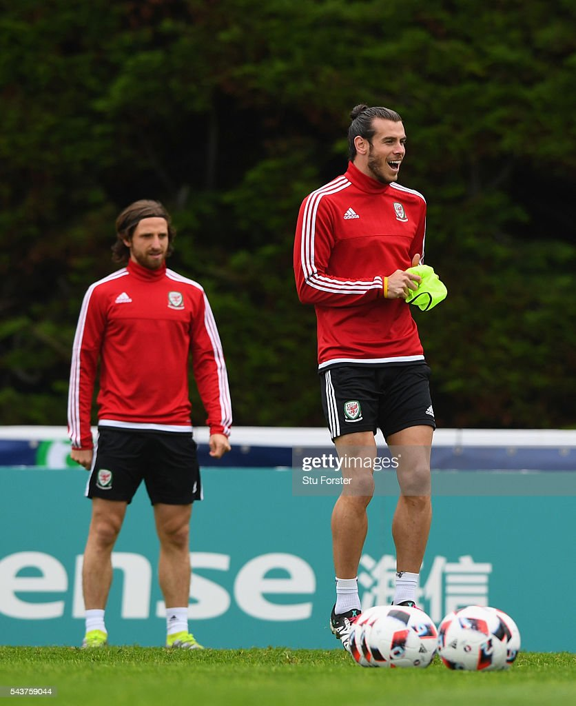 Wales player <a gi-track='captionPersonalityLinkClicked' href=/galleries/search?phrase=Gareth+Bale&family=editorial&specificpeople=609290 ng-click='$event.stopPropagation()'>Gareth Bale</a> (with bib) shares a joke with team mates during Wales training session ahead of their Euro 2016 quarter final match against Belgium at their base camp on June 30, 2016 in Lille, France.
