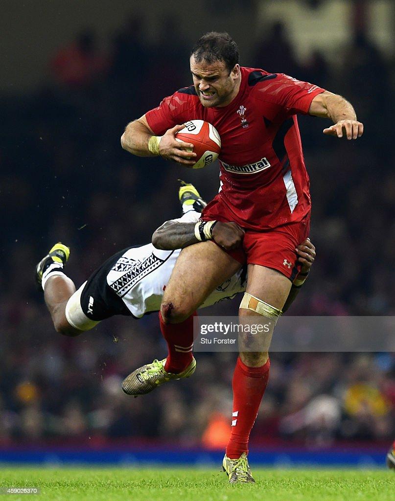 Wales player Jamie Roberts bursts through the challenge of Api Ratuniyarawa of Fiji during the International match between Wales and Fiji at Millennium Stadium on November 15, 2014 in Cardiff, Wales.
