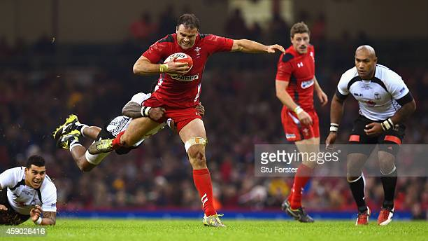 Wales player Jamie Roberts bursts through the challenge of Api Ratuniyarawa of Fiji during the International match between Wales and Fiji at...