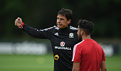 Wales player Neil Taylor listens to manager Chris Coleman during Wales training at the Vale hotel complex on June 1 2016 in Cardiff Wales