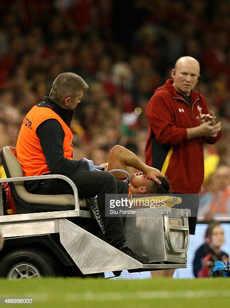 Wales player Rhys Webb is stretchered off as coach Neil Jenkins looks on during the International match between Wales and Ireland at Millennium...