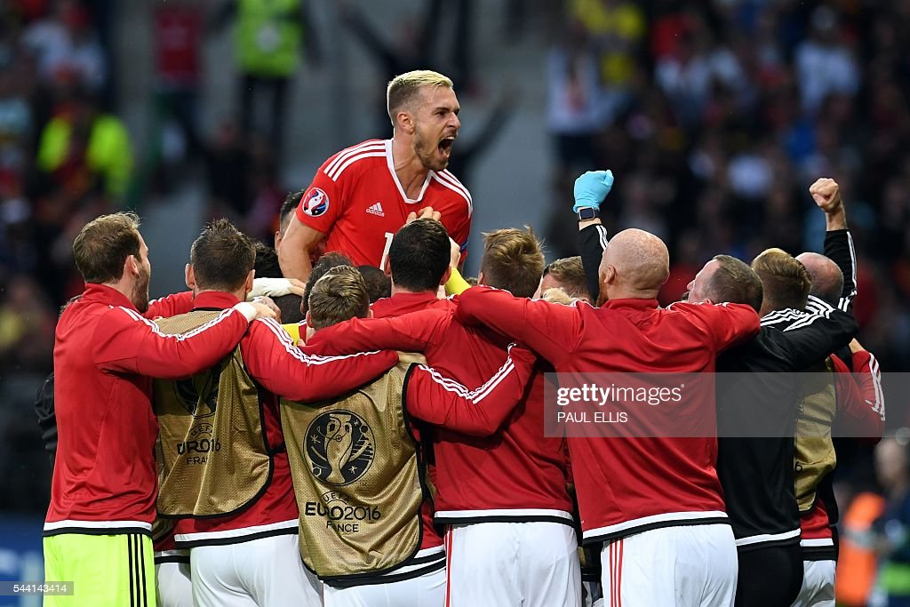 Wales' players celebrate after a goal by Wales' defender Ashley Williams during the Euro 2016 quarter-final football match between Wales and Belgium at the Pierre-Mauroy stadium in Villeneuve-d'Ascq near Lille, on July 1, 2016. / AFP / PAUL