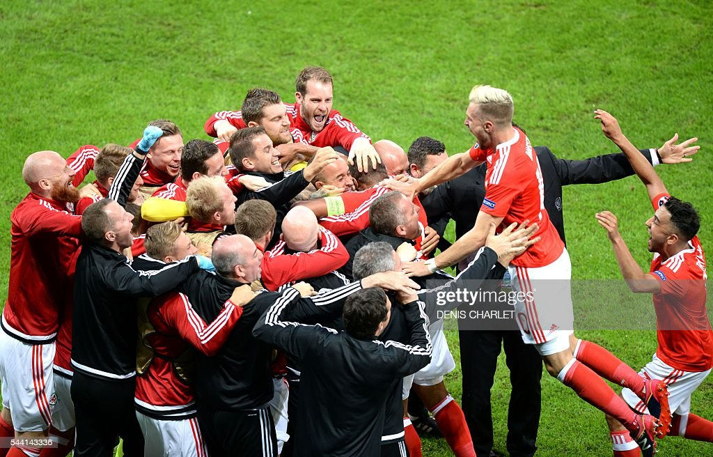 Wales' players celebrate after scoring a goal during the Euro 2016 quarter-final football match between Wales and Belgium at the Pierre-Mauroy stadium in Villeneuve-d'Ascq near Lille, on July 1, 2016. / AFP / Denis Charlet