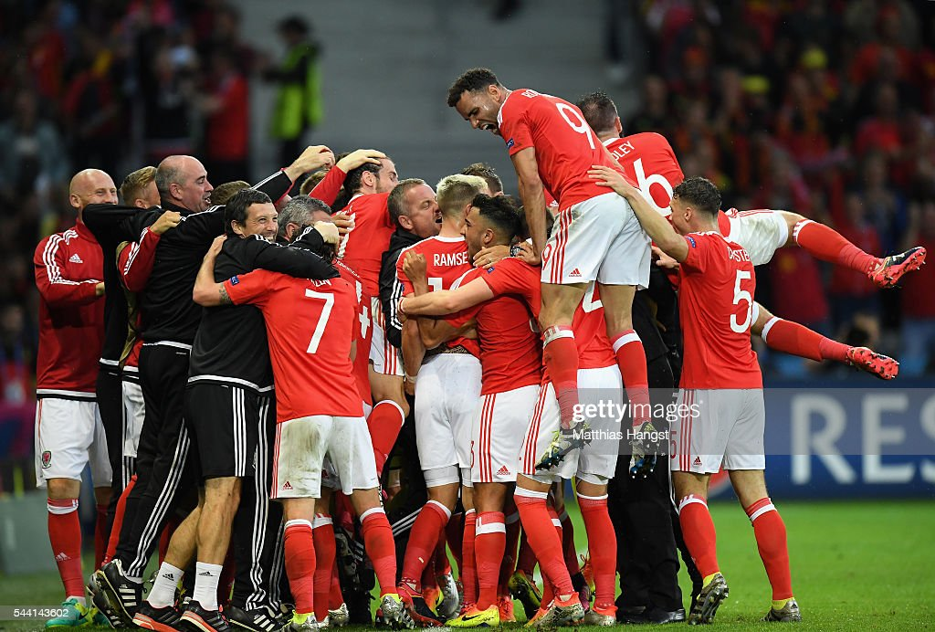 Wales players celebrate their team's first goal by Ashley Williams (obscured) during the UEFA EURO 2016 quarter final match between Wales and Belgium at Stade Pierre-Mauroy on July 1, 2016 in Lille, France.