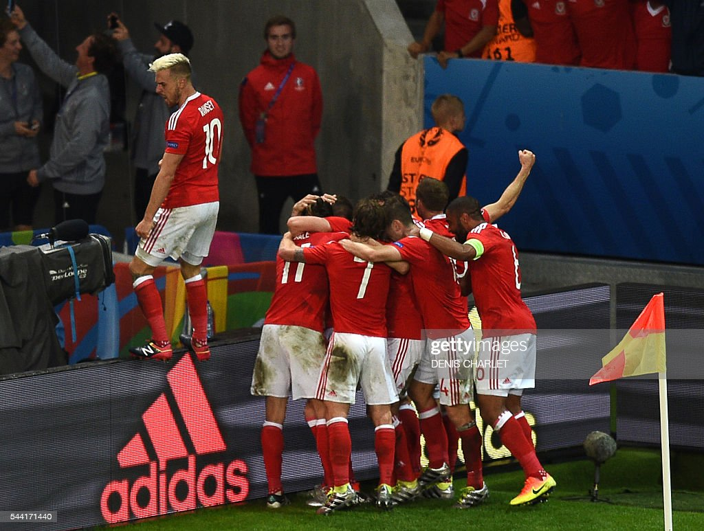 Wales' players celebrate their third goal during the Euro 2016 quarter-final football match between Wales and Belgium at the Pierre-Mauroy stadium in Villeneuve-d'Ascq near Lille, on July 1, 2016. / AFP / DENIS
