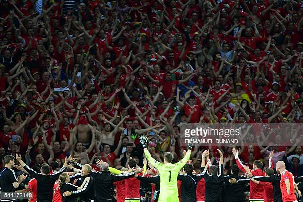 TOPSHOT Wales' players celebrate with supporters after the Euro 2016 quarterfinal football match between Wales and Belgium at the PierreMauroy...