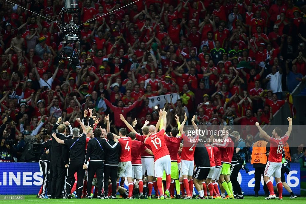 Wales' players celebrate with supporters after the Euro 2016 quarter-final football match between Wales and Belgium at the Pierre-Mauroy stadium in Villeneuve-d'Ascq near Lille, on July 1, 2016. Wales won the match 3-1. / AFP / EMMANUEL