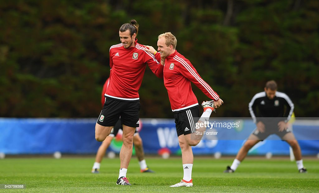 Wales players <a gi-track='captionPersonalityLinkClicked' href=/galleries/search?phrase=Gareth+Bale&family=editorial&specificpeople=609290 ng-click='$event.stopPropagation()'>Gareth Bale</a> (l) and Jonathan Williams stretch during Wales training session ahead of their Euro 2016 quarter final match against Belgium at their base camp on June 30, 2016 in Lille, France.