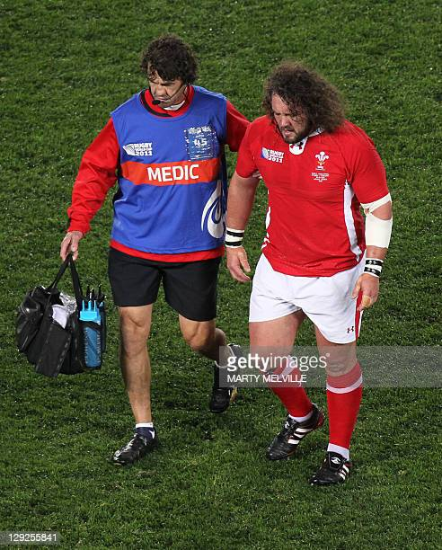 Wales' prop Adam Jones is assisted off the field after an injury during the 2011 Rugby World Cup semifinal match France vs Wales at Eden Park Stadium...