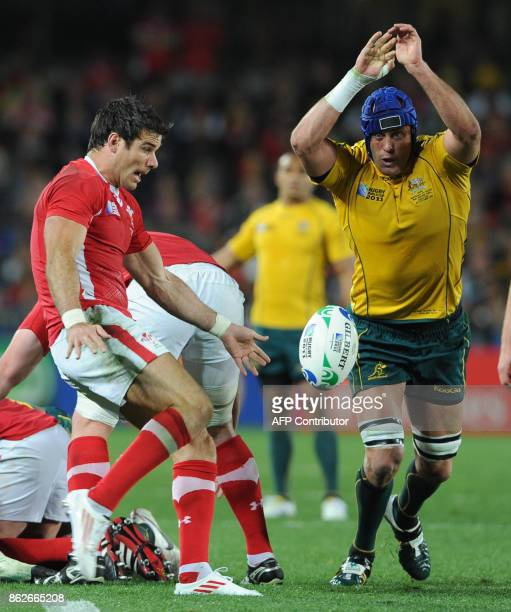 Wales' scrumhalf Michael Phillips kicks the ball next to Australian Wallabies lock James Horwill during the 2011 Rugby World Cup bronze final match...