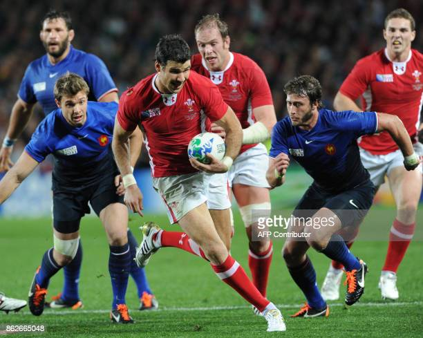 Wales' scrumhalf Mike Phillips runs to score ahead of France's right wing Vincent Clerc and France's center Maxime Mermoz during the 2011 Rugby World...