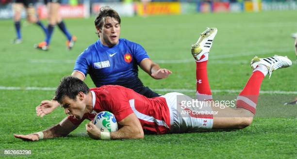 Wales' scrumhalf Mike Phillips scores a try in front of France's left wing Alexis Palisson during the 2011 Rugby World Cup semifianl match Wales vs...