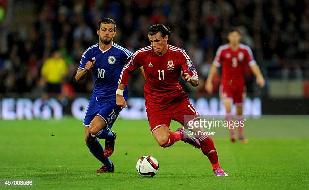 Wales striker Gareth Bale races past Bosnia player Miralem Pjanic during the EURO 2016 Qualifier match between Wales and Bosnia and Herzegovina at...