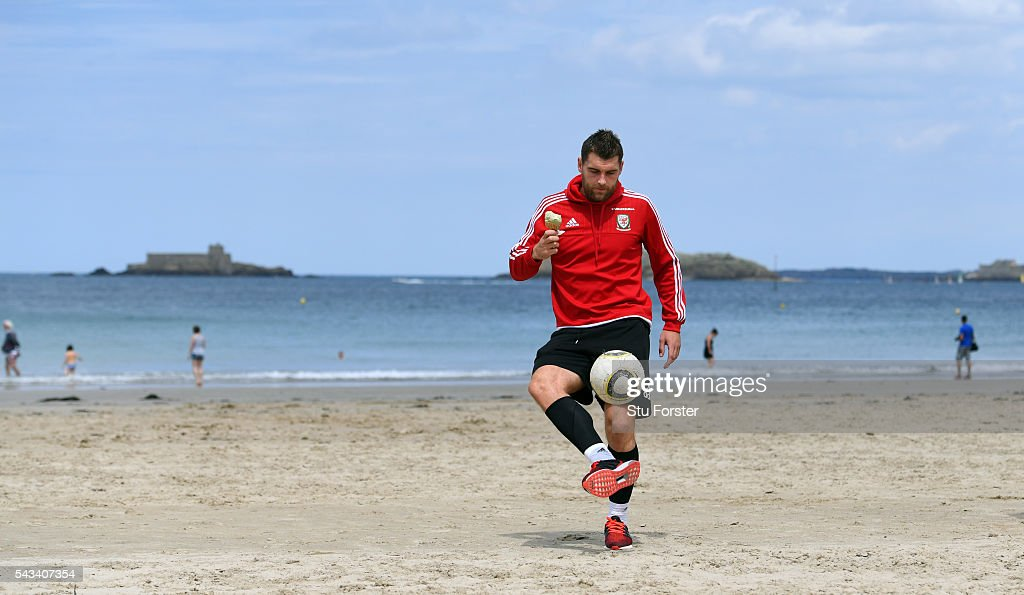 Wales striker <a gi-track='captionPersonalityLinkClicked' href=/galleries/search?phrase=Sam+Vokes&family=editorial&specificpeople=4778614 ng-click='$event.stopPropagation()'>Sam Vokes</a> enjoys an Ice Cream whilst juggling a football on Dinard beach on June 28, 2016 in Dinard, France.