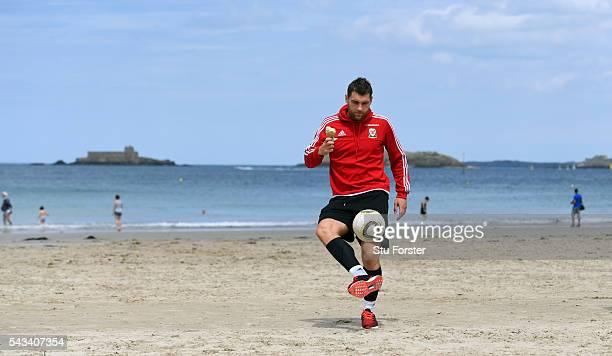 Wales striker Sam Vokes enjoys an Ice Cream whilst juggling a football on Dinard beach on June 28 2016 in Dinard France