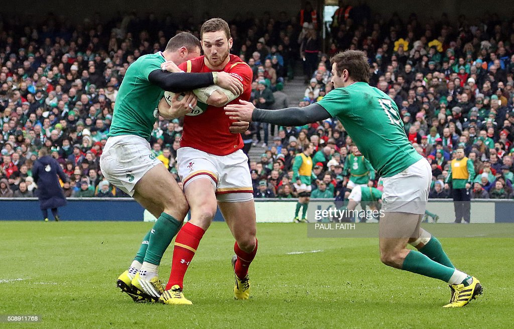 Wales' wing George North (C) vies with Ireland's centre Jared Payne (R) during the Six Nations international rugby union match between Ireland and Wales at the Aviva Stadium in Dublin, Ireland, on February 7, 2016. / AFP / PAUL FAITH
