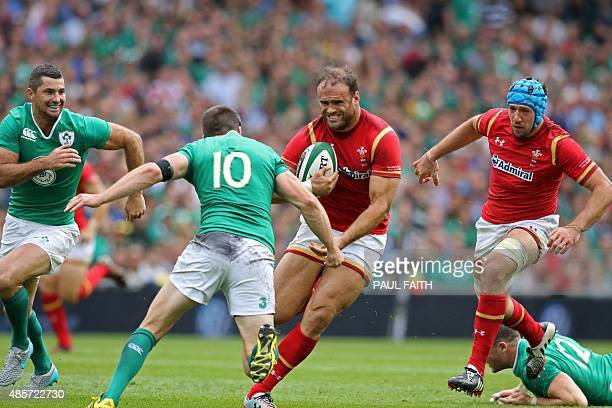 Wales's centre Jamie Roberts is tackled by Ireland's fly half Johnny Sexton during the 2015 Rugby World Cup warm up match between Ireland and Wales...