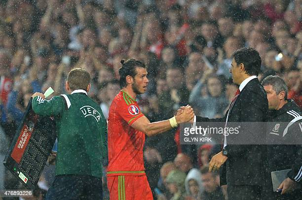 Wales's midfielder Gareth Bale shakes hands with Wales's manager Chris Coleman as Bale was substituted after picking up a knock at the end of the...