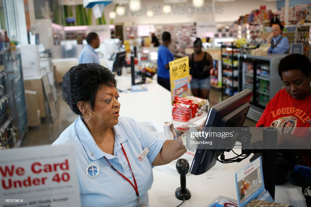 Walgreen Co. cashier June White rings up a customer at one of the company's stores in Louisville, Kentucky, U.S., on Monday, Sept. 30, 2013. Walgreen Co., the biggest U.S. drugstore chain, is expected to report fourth-quarter earnings before the opening of U.S financial markets on Oct. 1. Photographer: Luke Sharrett/Bloomberg via Getty Images