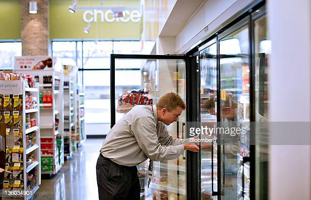 Walgreens Co Store Manager Mark Tomic stocks items in the frozen food section of a store in Oak Park Illinois US on Tuesday Dec 20 2011 Walgreen Co...
