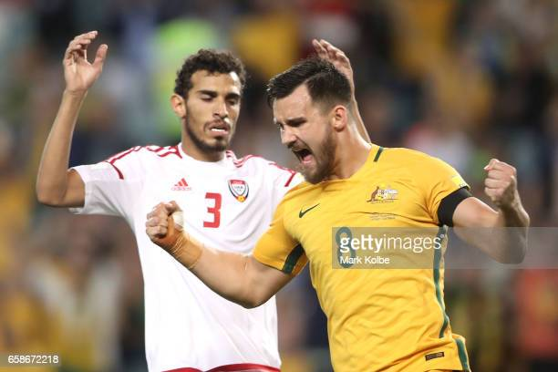 Walid Abbas of the United Arab Emirates looks dejected as Bailey Wright of the Socceroos celebrates Jackson Irvine scoring a goal during the 2018...