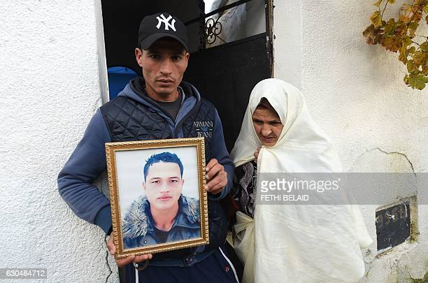 Walid Amri the brother of 24yearold Anis Amri the prime suspect in Berlin's deadly truck attack poses with a portrait of his brother in front of the...