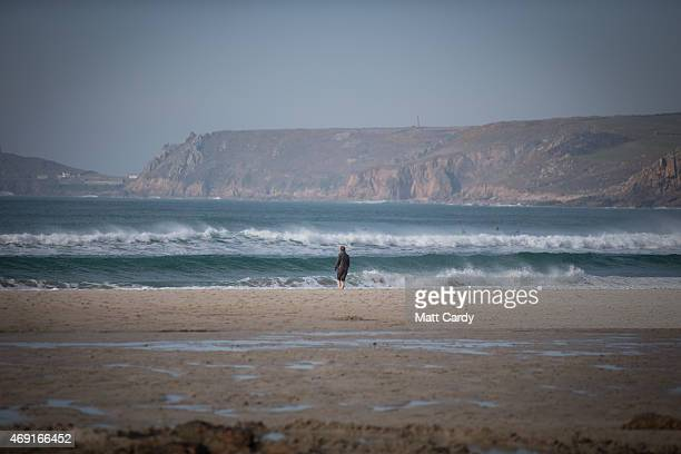 A walker looks at the waves breaking at Sennen Cove on April 9 2015 in Cornwall England Prime Minister David Cameron has said that the six seats in...