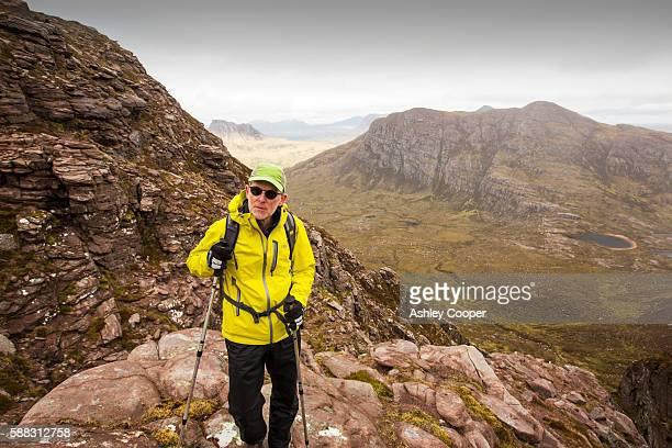 A walker on Ben Mor Coigach, looking towards Stac Pollaidh near Ullapool, Scotland, UK.