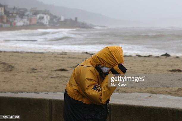 A walker pulls down their hood as they braves the stormy weather on December 23 2013 in Lyme Regis England The Met Office has issued a number of...