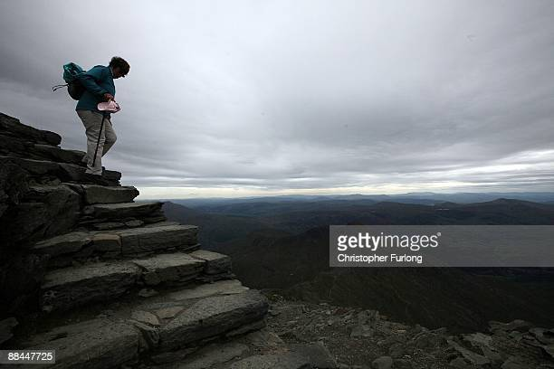 A walker stands on the summit of Mount Snowdon on June 12 2009 in Llanberis Wales The new £84m visitor centre and cafe on the summit of Snowdon was...